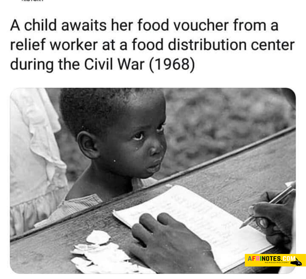 A child awaits her food voucher from a relief worker at a food distribution center during the Nigeria and Biafra Civil war in the year 1968