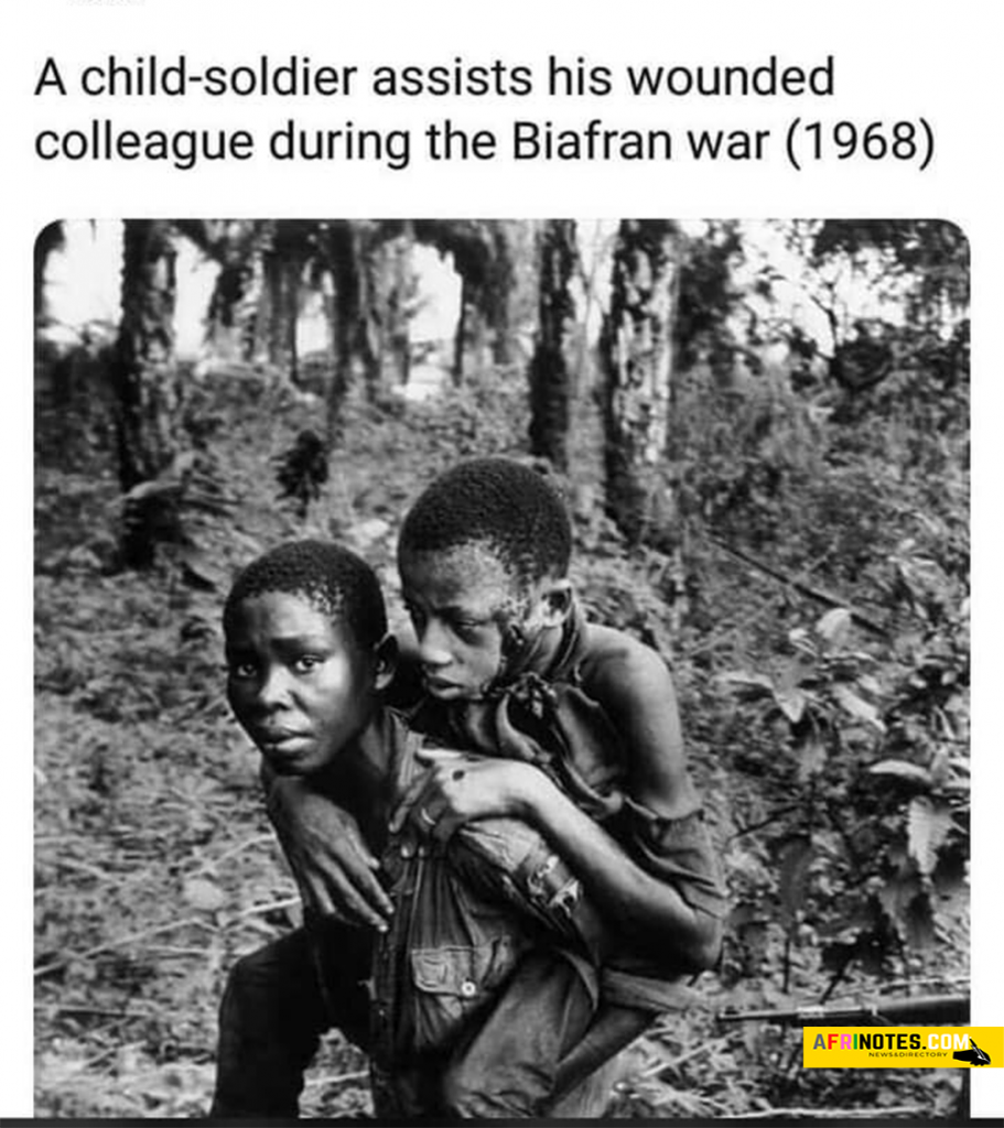 A child soldier assists his wounded colleague during Biafra was in the year 1968